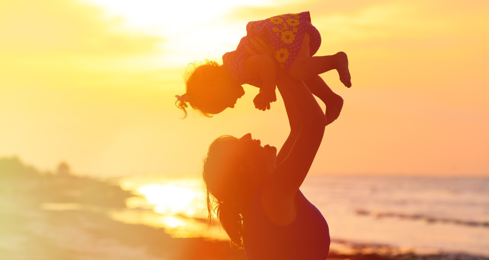 happy mother and little daughter play at sunset